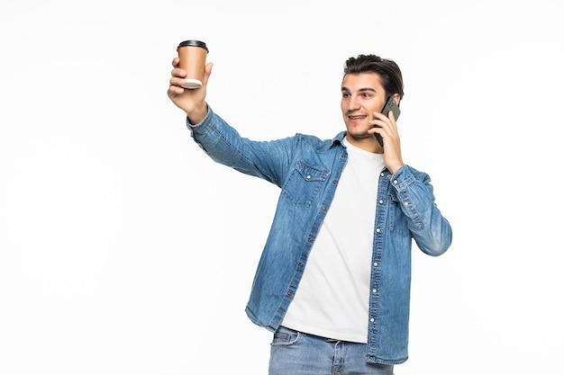 Portret szczęśliwy człowiek rozmawia przez telefon i pije herbatę lub kawę na białym tle na białym backgorund