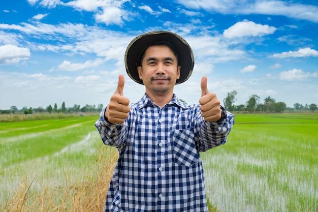 Portret szczęśliwy człowiek się uśmiecha. rolnik kciuk w górę stoi w koszuli