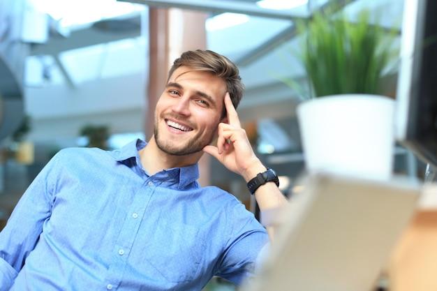 Portret szczęśliwy człowiek siedzi przy biurku, patrząc na kamery, uśmiecha się.