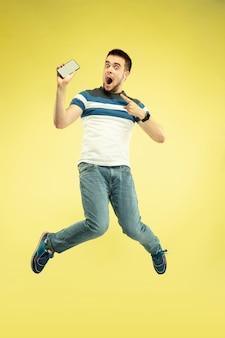 Portret szczęśliwy człowiek skaczący z gadżetami na żółtej ścianie