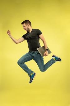 Portret szczęśliwy człowiek skoki z gadżetami na żółtym tle
