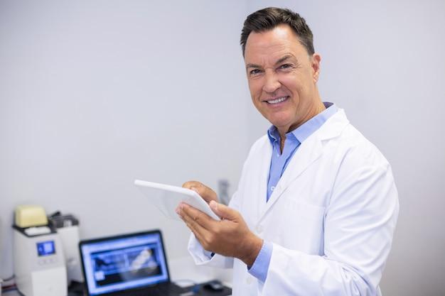 Portret szczęśliwy dentysta za pomocą cyfrowego tabletu