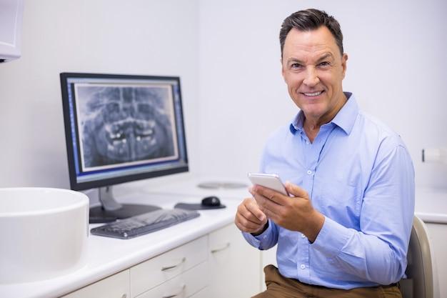 Portret szczęśliwy dentysta za pomocą telefonu komórkowego