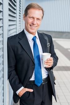Portret szczęśliwy dojrzały biznesmen z filiżanką kawy
