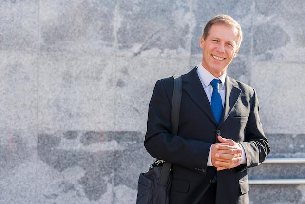 Portret szczęśliwy dojrzały biznesmen z spinać rękami