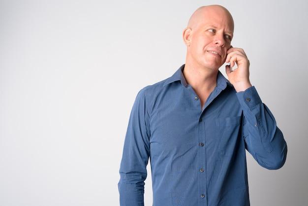 Portret szczęśliwy dojrzały łysy biznesmen rozmawia przez telefon