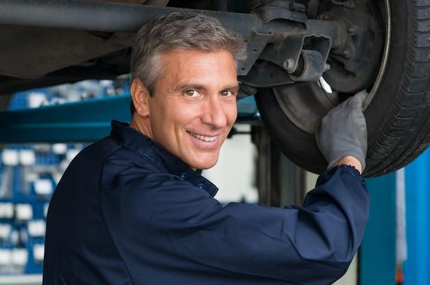 Portret szczęśliwy dojrzały mechanik na stacji serwisowej