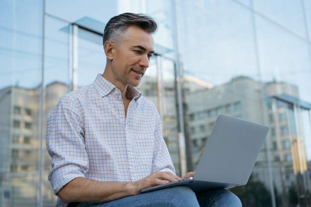 Portret szczęśliwy dojrzały programista za pomocą laptopa, działający projekt