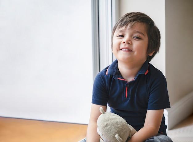 Portret szczęśliwy dzieciak siedzi na drewnianej podłodze, bawi się z misiem, ładny chłopiec bawić się swoją pluszową zabawką