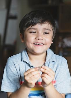 Portret szczęśliwy dzieciak spogląda z uśmiechniętą twarz, dziecko grające samotnie w salonie