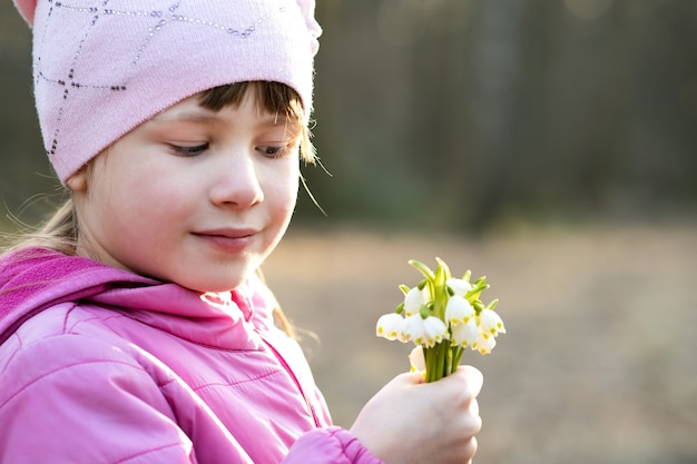 Portret szczęśliwy dziecko dziewczyna trzyma bukiet przebiśnieg wczesną wiosną kwiaty na zewnątrz