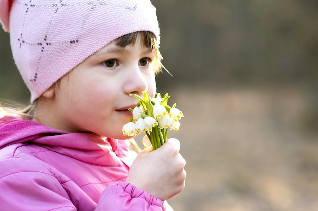 Portret szczęśliwy dziecko dziewczyna trzyma bukiet przebiśnieg wczesną wiosną kwiaty na zewnątrz.