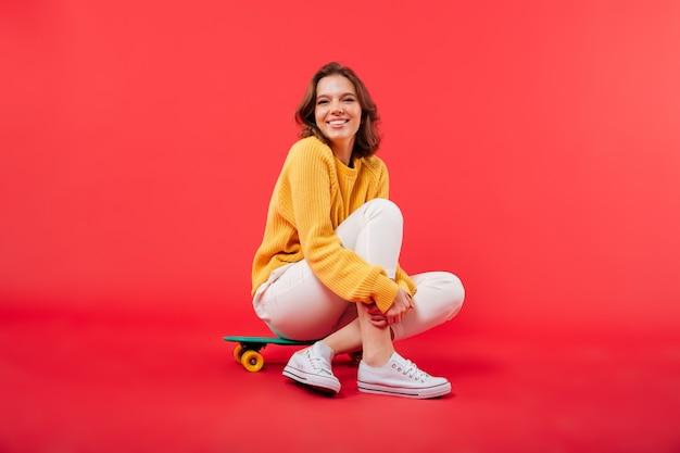 Portret szczęśliwy dziewczyny siedzącej na deskorolce