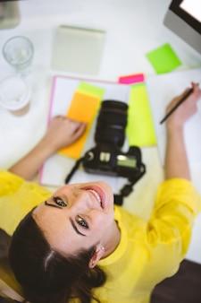 Portret szczęśliwy edytor zdjęć siedzi w biurze