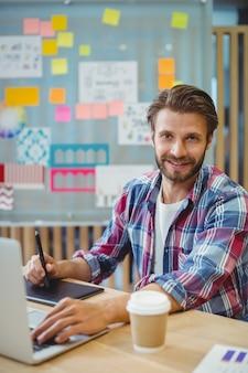 Portret szczęśliwy grafik za pomocą laptopa i tabletu graficznego
