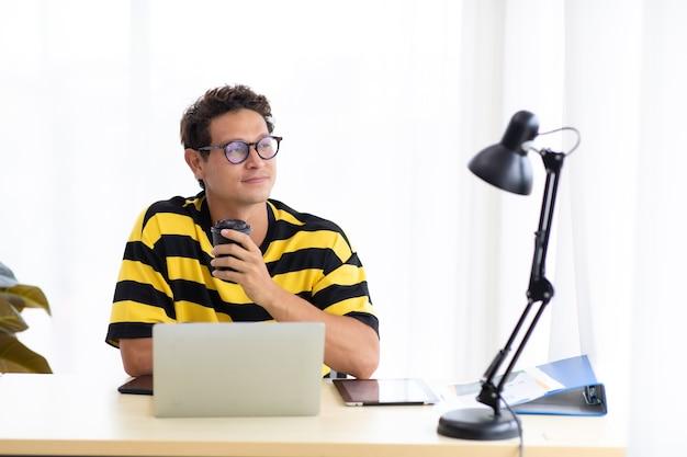 Portret szczęśliwy hiszpanin kreatywny człowiek picia kawy i pracy na komputerze przenośnym w nowoczesnym biurze domowym.