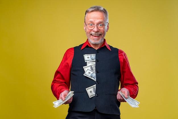 Portret szczęśliwy i białe zęby uśmiech starszy stary człowiek biznesu trzyma pieniądze w ręce, ubrany w czerwoną koszulę, na białym tle na żółtym tle. ludzkie emocje i mimika twarzy