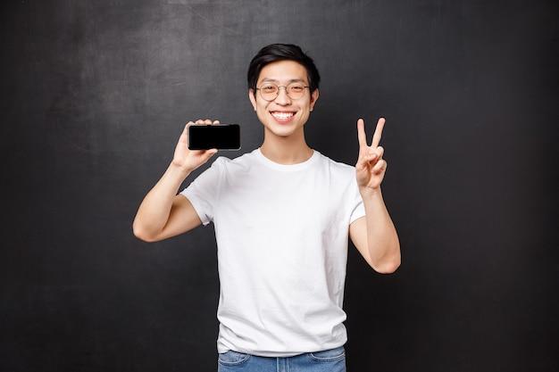 Portret szczęśliwy i zadowolony młody azjatycki facet trzyma smartfona i robi znak zwycięstwa