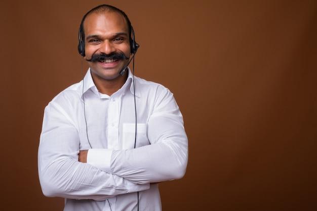 Portret szczęśliwy indyjski biznesmen z wąsem jako przedstawiciel call center