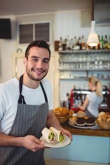 Portret szczęśliwy kelner z świeżymi rolkami przy kawiarnią