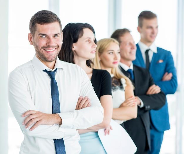 Portret szczęśliwy kierownik z jego pracownikami stoi z rzędu