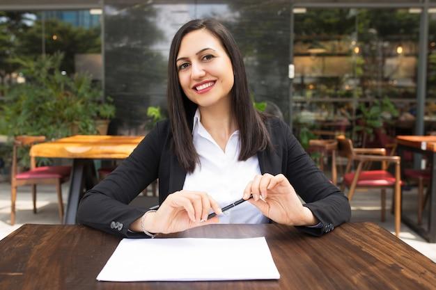 Portret szczęśliwy kierownika obsiadanie z piórem i papier przy kawiarnią
