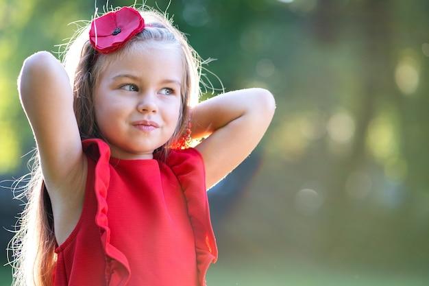 Portret szczęśliwy ładne dziecko dziewczyna uśmiechający się na zewnątrz, ciesząc się ciepły słoneczny letni dzień.