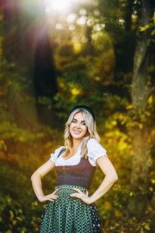 Portret szczęśliwy ładny blond dziewczyna w dirndl, tradycyjny strój festiwalu piwa, stojący na zewnątrz z blured kolorowe drzewa za