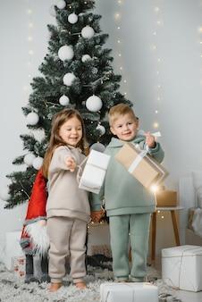 Portret szczęśliwy ładny mały kaukaski chłopiec i dziewczynka dzieci pozują w pobliżu udekorowanej choinki. uśmiechający się mały brat i siostra bawią się świętując nowy rok w przytulnym domu.