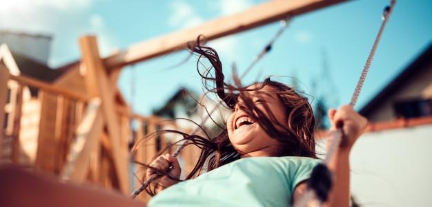 Portret szczęśliwy małej dziewczynki siedzącej na huśtawce i uśmiechnięty
