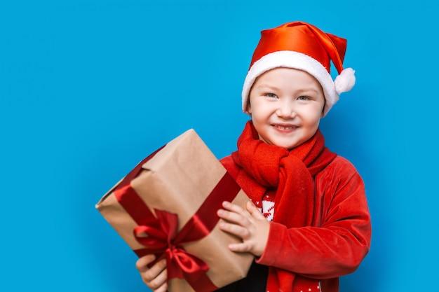 Portret szczęśliwy mały chłopiec trzyma nowy prezent na boże narodzenie