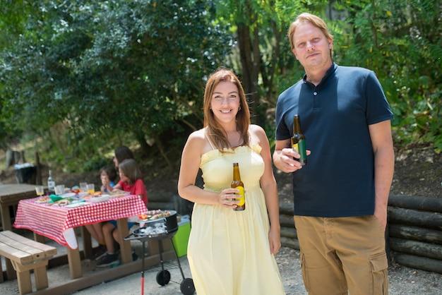 Portret szczęśliwy mąż i żona pije piwo przy piknikiem. średni dorosły mężczyzna i kobieta uśmiechający się, trzymający butelki z piwem