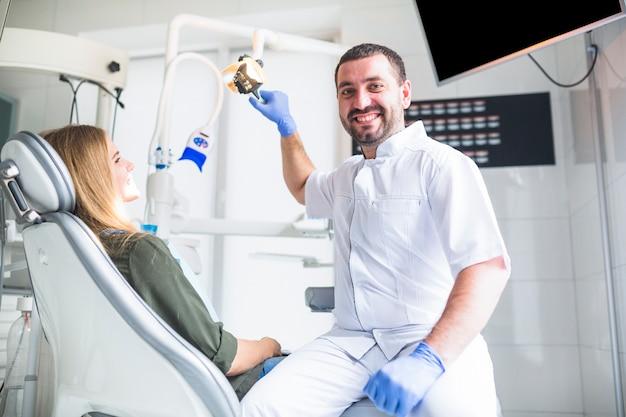 Portret szczęśliwy męski dentysta egzamininuje kobieta zęby