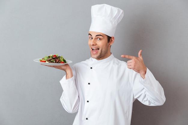Portret szczęśliwy męski szef kuchni ubierał w mundurze