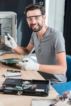 Portret szczęśliwy męski technik pracuje na komputerowej płycie głównej