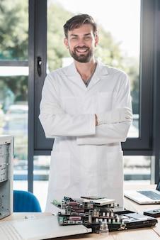 Portret szczęśliwy męski technik z krzyżować rękami stoi w warsztacie