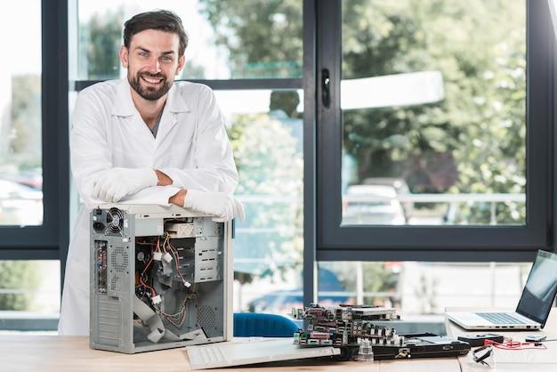 Portret szczęśliwy męski technik z łamanym komputerem