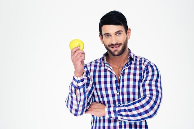 Portret szczęśliwy mężczyzna lekkoatletycznego gospodarstwa jabłko na białym tle na białej ścianie