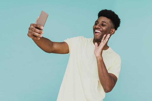 Portret szczęśliwy mężczyzna o rozmowie wideo ze smartfonem