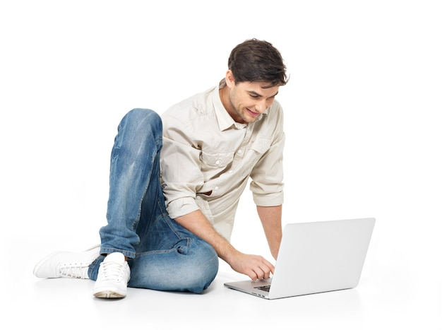 Portret szczęśliwy mężczyzna pracuje na laptopie w przypadkowym odizolowywającym na bielu. komunikacja koncepcyjna.