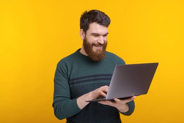 Portret szczęśliwy mężczyzna surfuje na internecie stoi nad kolor żółty ścianą