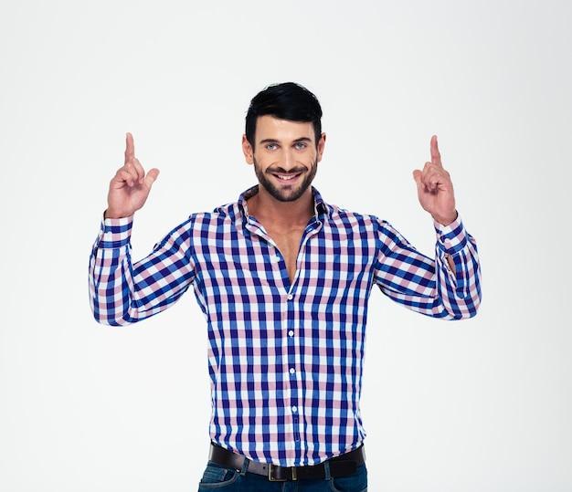 Portret szczęśliwy mężczyzna wskazując palcami w górę na copyspace na białym tle na białej ścianie