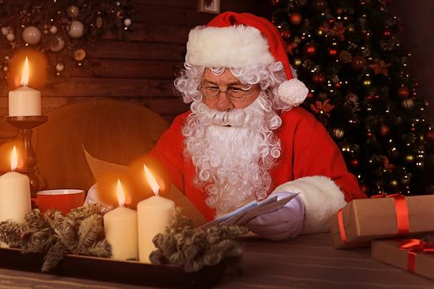 Portret szczęśliwy mikołaj siedzi w swoim pokoju w domu w pobliżu choinki i czyta list bożonarodzeniowy lub listę życzeń.