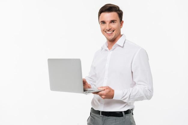Portret szczęśliwy młodego człowieka mienia laptop