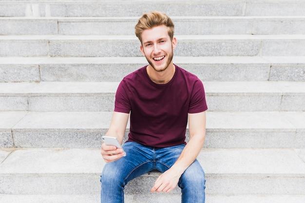 Portret szczęśliwy młodego człowieka mienia telefon komórkowy