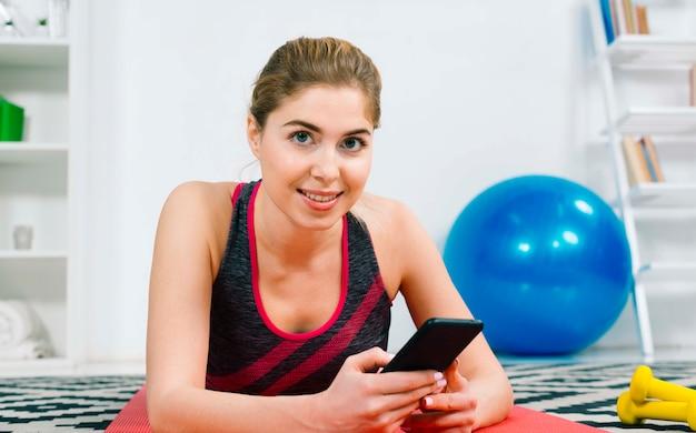 Portret szczęśliwy młodej kobiety mienia telefon komórkowy w ręce patrzeje kamerę