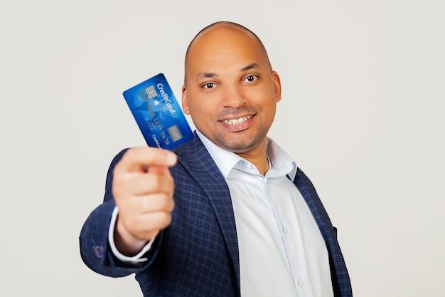 Portret szczęśliwy młody african american biznesmen facet trzyma kartę kredytową z radosną twarzą, stoi i uśmiecha się z pewnym uśmiechem pokazując zęby.
