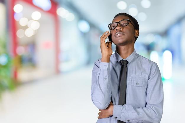 Portret szczęśliwy młody afrykański mężczyzna z telefonem komórkowym