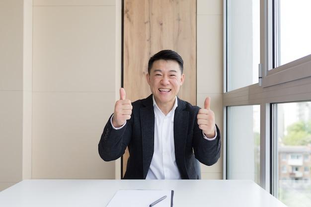 Portret szczęśliwy młody azjatycki mężczyzna urzędnik patrząc na kamery i uśmiechając się w pomieszczeniu. zbliżenie na przyjazny menedżer w garniturze i białej koszuli siedzi w pracy. biznesmen czujący, że otrzymuje