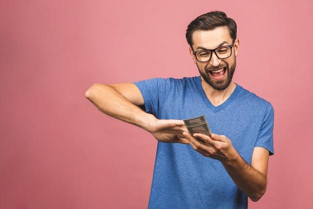 Portret szczęśliwy młody biznesmen rzuca out pieniędzy banknoty odizolowywających nad różowym tłem.